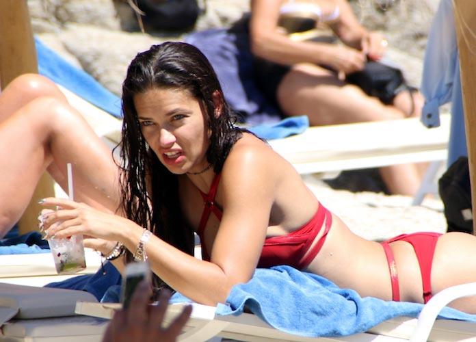 Adriana Lima Sunbathes With A Drink In Mykonos